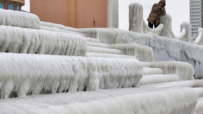 Ice age ... A local resident takes photos of stairs covered by ice in Yantai city, in east China's Shandong province. Picture: Splash