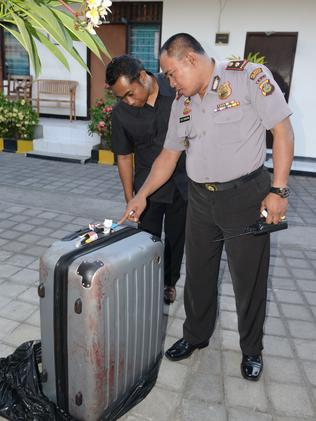 A policeman looking at a suitcase where a woman's body was found inside. Picture: AFP