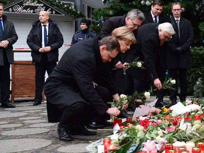 Berlin's mayor Michael Mueller, German Chancellor Angela Merkel, Interior Minister Thomas de Maiziere and Foreign Minister Frank-Walter Steinmeier lay flowers at a makeshift memorial. Picture: AFP
