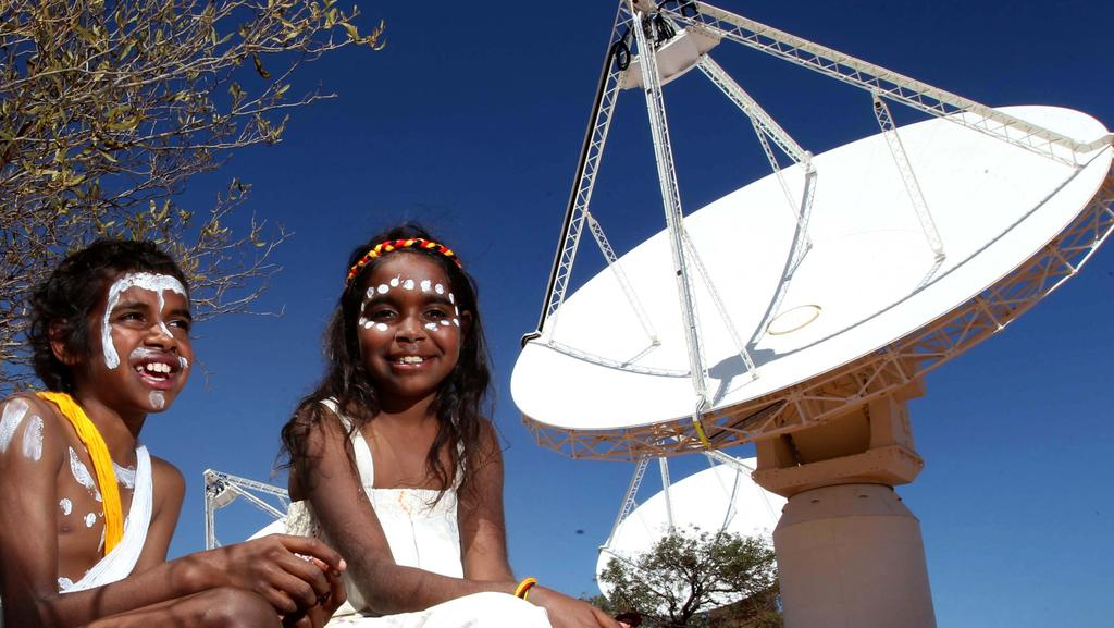 Local Wajarri children Zac George and Josephine Demi in front of the ASKAP antenna at the Array Pathfinder at the Murchison Radio Astronomy Observatory. Picture: Colin Murty