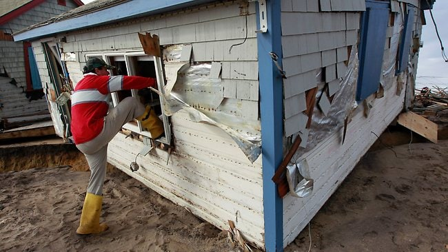 Christopher Hannafin enters a friend's cottage through a window to salvage belongings from the structure destroyed by Superstorm Sandy, on Roy Carpenter's Beach, in the village of Matunuck, in South Kingstown. Picture: Steven Senne
