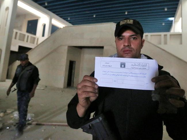 "A member of the Iraqi government forces holds an envelope from the office of the self-proclaimed Islamic State (IS) group charity and alms office calling for the rich to donate to the poor, which is known in Islam as ""Zakat"". Picture: Ahmad Al-Rubaye"