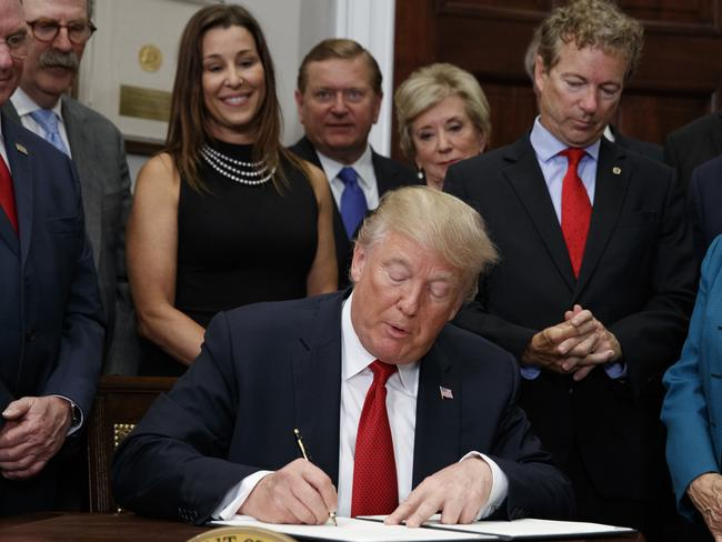 President Donald Trump signs an executive order on health care in the Roosevelt Room of the White House. Picture: AP
