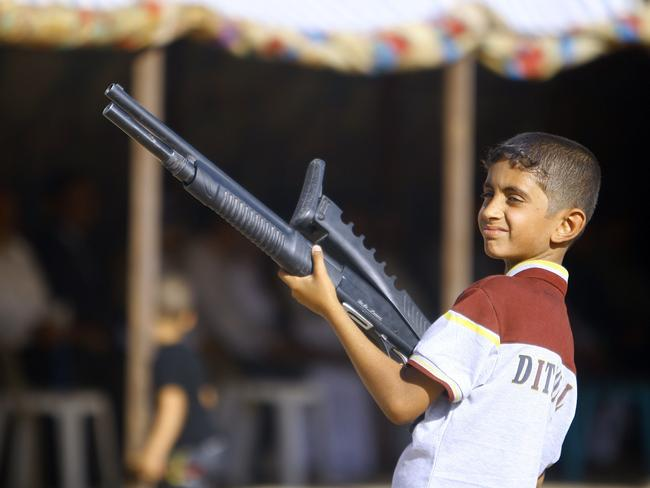 An Iraqi boy holds a weapon as he takes part in a gathering by Shiite tribesman to show their willingness to join Iraqi security forces in the fight against Jihadist militants. AFP PHOTO/HAIDAR HAMDANI