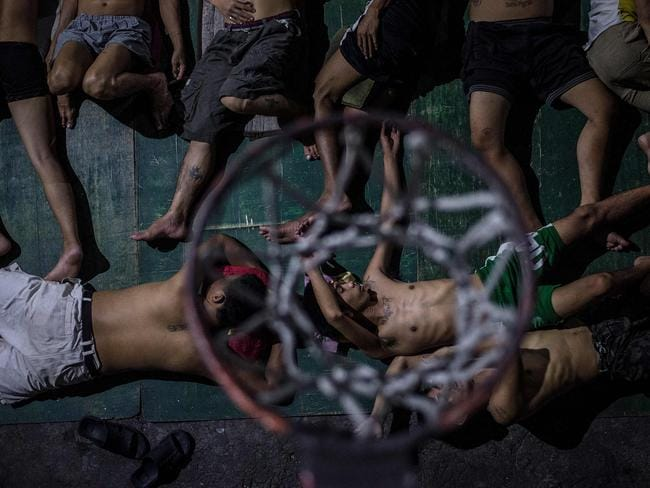Inmates sleep on the ground of an open air basketball court inside the Quezon City jail at night in Manila. Picture: Ayee Macaraig