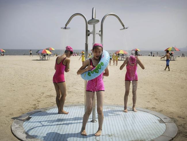 North Korean girls in similar bathing suits stand under a shower at the Songdowon International Children's Camp, last month.