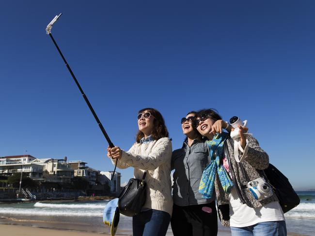Korean tourists Julie Kim, Claire Kim and Kyunghwa Jung doing a joint selfie in the sun shine this morning at Bondi Beach but they better be quick with the weather due to turn.