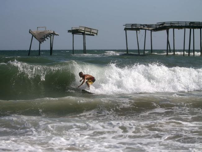 Surfers warned to keep out of the water ... Stephen Hunter Hicks surfs near Hatteras Pier, damaged in previous hurricanes, in Cape Hatteras, North Carolina.