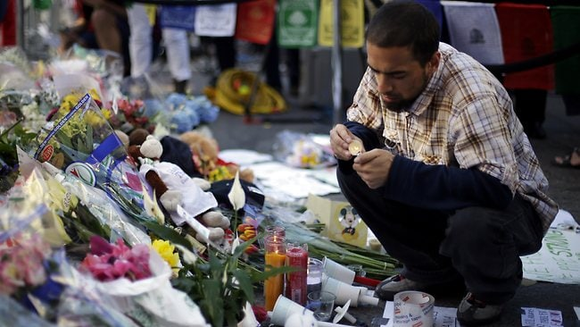 Richard Maldonado lights a candle at a makeshift memorial on Boylston Street near the finish line of Monday's Boston Marathon explosions, which killed at least three and injured more than 140, Wednesday, April 17, 2013, in Boston. (AP Photo/Matt Rourke)