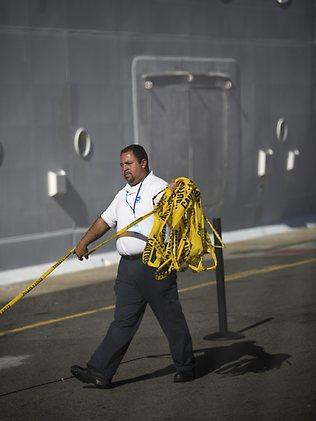 An official removes a yellow caution barricade tape from around the Royal Caribbean International's Explorer of the Seas crusie ship, on which hundreds of passengers have fallen sick. Picture: AP