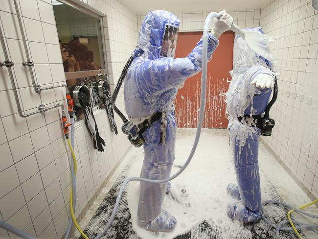 Drills ... a nurse and a doctor wearing isolation suits demonstrate the Ebola decontamination procedure.