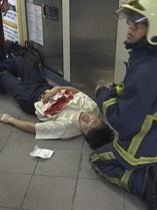 Paramedics tend to a victim stabbed on a subway train, in Taipei.