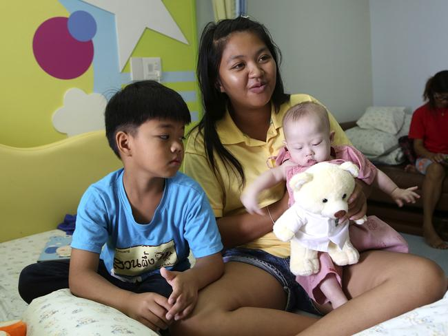 Family values ... surrogate mother Pattaramon Chanbua, 21, with her son Game, left, is raising baby boy Gammy with her other children. Picture: Apichart Weerawong