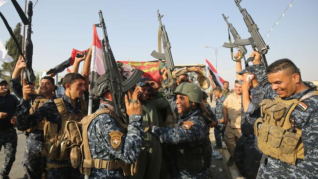 Iraqi federal police members flash their weapons in victory. Picture: AFP