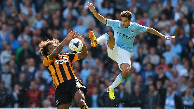 Jesus Navas of Manchester City tackles Tom Huddlestone of Hull City during the Barclays Premier League match between Manchester City and Hull City at the Etihad Stadium.
