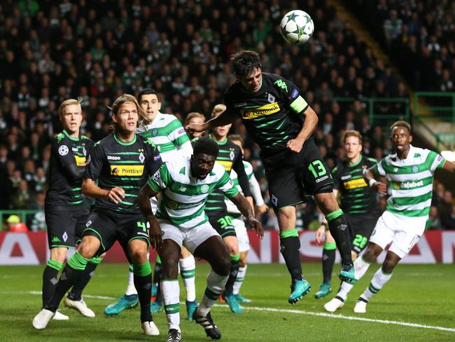 Moenchengladbach's Lars Stindl, center jumps for a header next to Celtic's Kolo Toure.