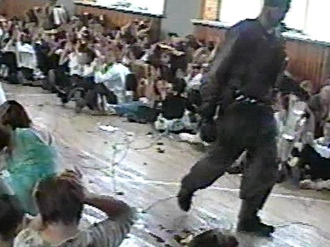 Innocence lost ... A video capture showing a militant with children being held hostage in the gymnasium of school in Beslan, Russia. Source: Supplied