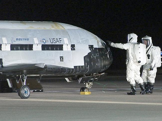 Pet project ... US Air Force personnel examine an X-37B after it returned from its space deployment.