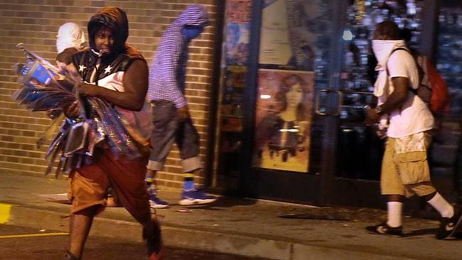 Looting again ... Looting began again in Ferguson after police and protesters clashed. Picture: AP/St. Louis Post-Dispatch, Robert Cohen