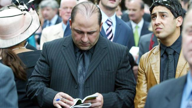 Tony Mokbel consults the form guide at Flemington racecourse on Oaks Day in 2004.