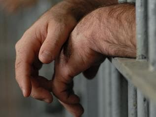 Man behind bars. Jail. Prison. Prisoner. Hands. Generic image.