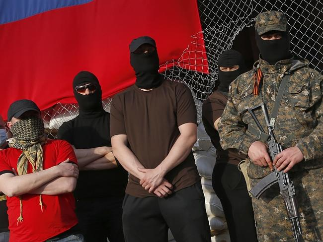 Masked pro-Russian armed men outside a city hall where negotiations continue over the release of foreign military observers being held by rebels. AP Photo/Sergei Grits