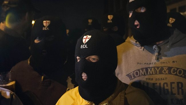 Members of the English Defence League (EDL) wear balaclavas as they gather outside a pub in Woolwich in London after a man believed to be a serving British soldier was brutally murdered nearby. AFP / Justin Tallis