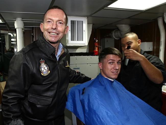 Meet and greet ... Tony Abbott in the barber shop on board the USS Blue Ridge. Picture: Tim Hunter.