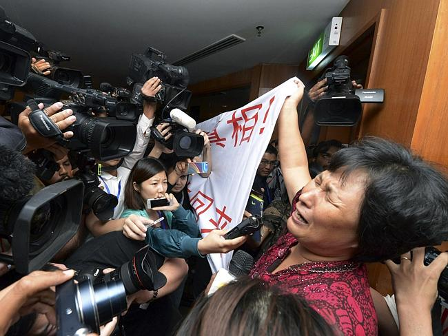 "A Chinese relative of passengers aboard the missing Malaysia Airlines plane cries and holds a banner which says: 'We are against the Malaysian government for hiding the truth and delaying the rescue. Release our families unconditionally!"" Picture: AP"