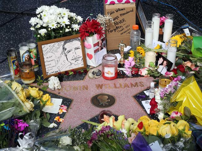 Flowers, photographs and candles surround the star of Robin Williams as part of a makeshift memorial along the Hollywood Walk of Fame.