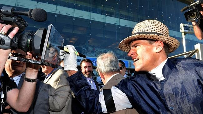 Fawkner jockey Nicholas Hall signs a camera after returning to scale. Picture: Jay Town