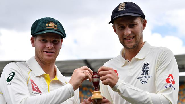 Australian skipper Steve Smith (left) and England captain Joe Root hold a replica Ashes Urn at the Gabba. Picture: AFP