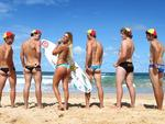 <p>Compare and contrast: Hawaiian surfer Alana Blanchard, in Sydney for the Australian Open of Surfing, with surf lifesavers from North Steyne. Picture: Brett Costello</p>
