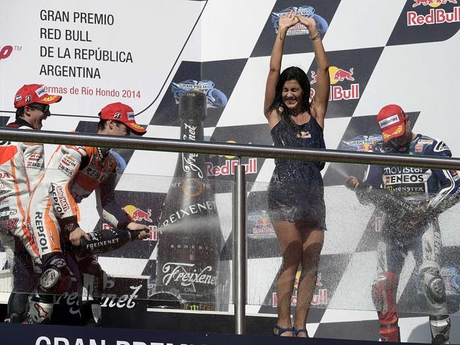 The top three spray the champagne on the podium.