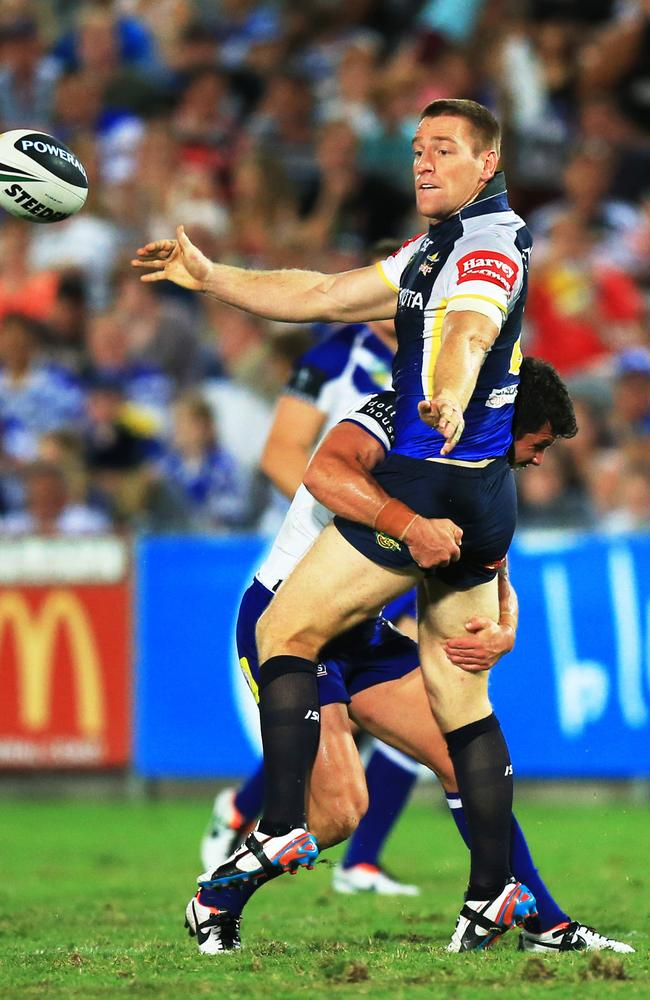 Brent Tate passes as he is tackled by Michael Ennis.