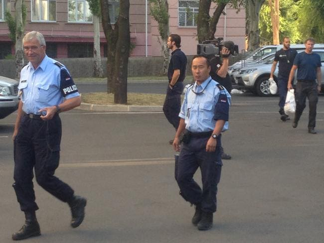 On their way ... Dutch and Malaysian police prepare to leave Donetsk on Friday morning. Picture: Paul Toohey