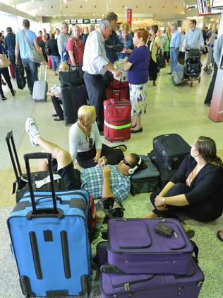 Passengers wait on the floor during delays at Melbourne Airport. Picture: Tim Carrafa