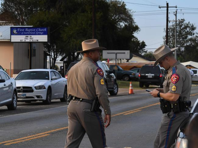 State troopers patrol at the entrance to the First Baptist Church (back) after a mass shooting that killed 26 people in Sutherland Springs, Texas on November 6, 2017 Picture: AP.