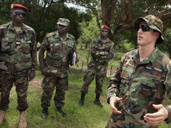 US Army special forces Captain Gregory, 29, from Texas, right, speaks with troops from the Central African Republic and Uganda who are searching for Joseph Kony's LRA. Picture: AP/Ben Curtis