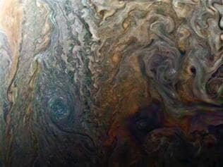 """This enhanced-color image of a mysterious dark spot on Jupiter seems to reveal a Jovian """"galaxy"""" of swirling storms. Juno acquired this JunoCam image on Feb. 2, 2017, at 5:13 a.m. PDT (8:13 a.m. EDT), at an altitude of 9,000 miles (14,500 kilometers) above the giant planet's cloud tops. This publicly selected target was simply titled """"Dark Spot."""" In ground-based images it was difficult to tell that it is a dark storm. Citizen scientist Roman Tkachenko enhanced the color to bring out the rich detail in the storm and surrounding clouds. Just south of the dark storm is a bright, oval-shaped storm with high, bright, white clouds, reminiscent of a swirling galaxy. As a final touch, he rotated the image 90 degrees, turning the picture into a work of art. Credits: NASA/JPL-Caltech/SwRI/MSSS/Roman Tkachenko"""