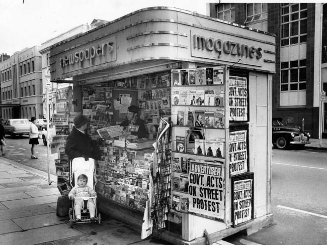 Pirie St Adelaide, 1970 — a woman with a baby in a stroller buys a copy of The Advertiser from one of then-common newspaper stands.