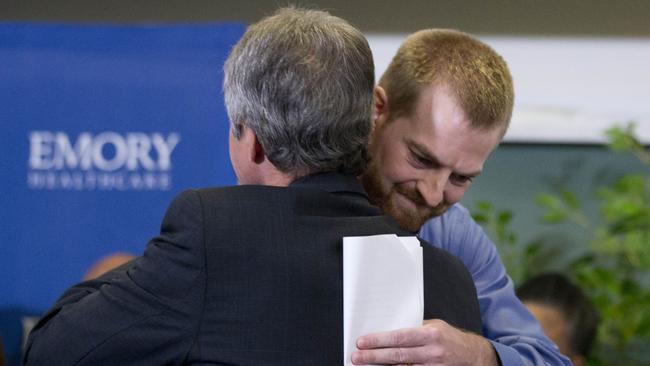 Heartfelt thanks ... Ebola victim Dr. Kent Brantly, right, hugs a member of the medical staff that treated him. Picture: AP Photo/John Bazemore