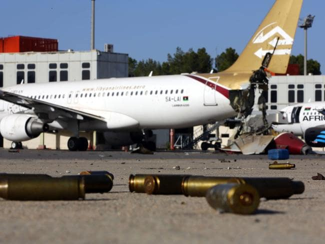 Battle damage ... bullet casings and damaged aircraft on the tarmac at Tripoli international airport. Picture: AFP PHOTO/MAHMUD TURKIA