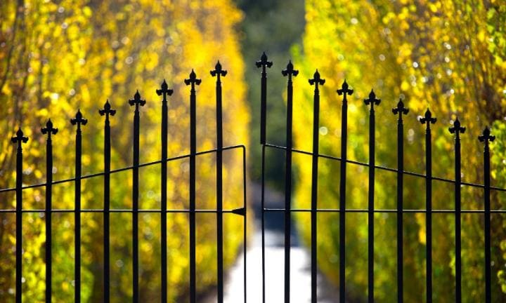 A closed wrought iron gate protects the entrance to an exclusive estate.