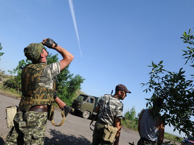 Battle rages ... Pro-Russia militants look overhead at a Ukrainian army plane as they exchange fire.
