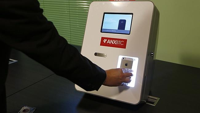 Ken Lo, CEO of ANXBTC Bitcoin Exchange scans his mobile QR code by a Bitcoin ATM. (AP Photo/Kin Cheung)