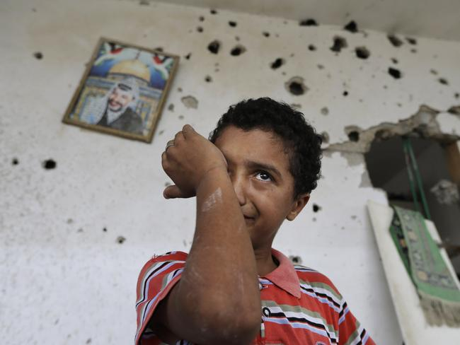 Tears ... Backdropped by a picture of late Palestinian leader Yasser Arafat, Palestinian boy Anas Shabat, 10, weeps as he inspects damages upon returning to his family house, destroyed by Israeli strikes in the town of Beit Hanoun, northern Gaza strip. Picture: AP