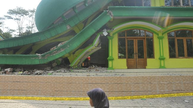 A woman passes a mosque that collapsed after a 6.1-magnitude quake rocked Java, Indonesia. Picture: Idhad Zakaria