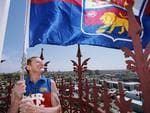 Kevin Murray raises the Brisbane Lions flag atop the Fitzroy town hall today after the 2001 Grand Final. Murray's father Dan played in the last Lions premiership side in 1944.