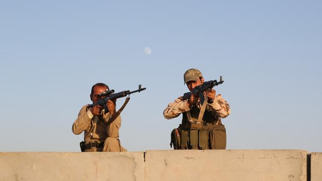 Kurdish Peshmerga fighters stand guard during airstrikes by the US forces targeting Islamic State militants at the Khazer checkpoint outside of the city of Irbil in northern Iraq. Picture: AP